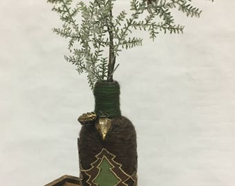 Yarn-wrapped Absolute Vodka bottle with felt tree ribbon and snow-flocked evergreen spray.