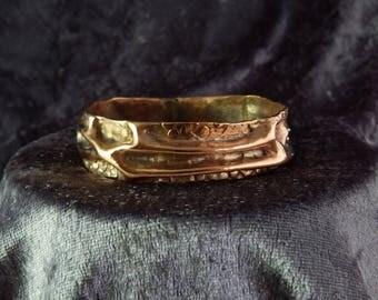 A handmade hammered copper bracelet.