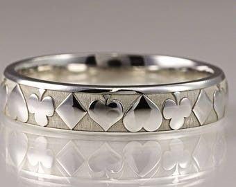 A platinum wedding ring with a laser engraved hearts diamonds clubs and spades motifs. hatton garden london jewellers