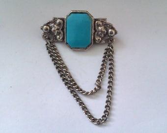 silver coloured blue stone brooch