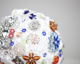 Multi color brooch bouquet with white ribbon.