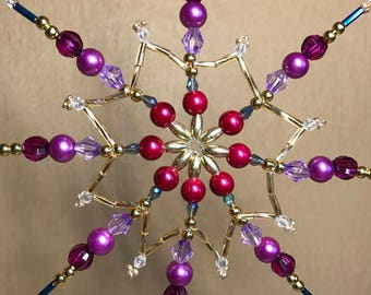 Eight-pointed star for a Christmas tree handmade. The ornament of shining beads in violet-golden tones. An exquisite gift for Christmas.