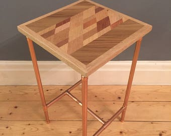 Side table in a retro industrial style with a copper pipe frame and reclaimed mixed hardwood geometric style top