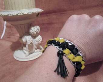 Bracelet of yellow and black fabric strips and metal color