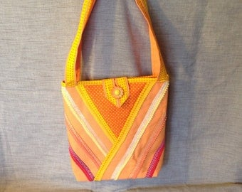 Orange canvas tote bag with ribbons and tassels in summer colors.