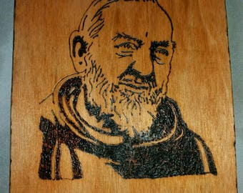 Burning painting by hand. San Pio