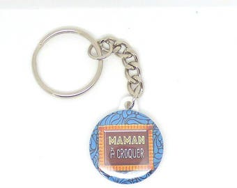 "a silver button ""mum to eat"" keychain"