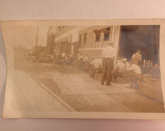 Nice black and white pocket photograph of depression era workers eating lunch outside of their factory