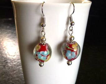 Earrings in red background with yellow, pink and blue flowers lampwork glass beads mounted on silver-plated hooks