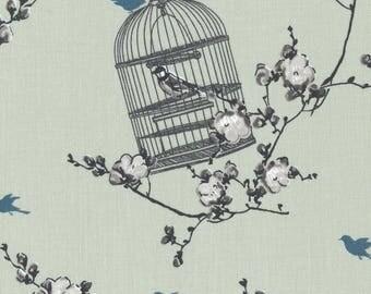 Toile cirée coton enduit motif imprimé cages et oiseaux sur pommiers en fleurs vendu a la coupe
