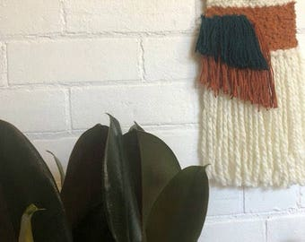 Burnt orange and teal woven wall hanging