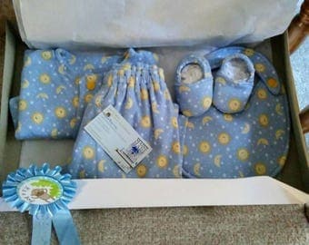 Newborn boy Pajama set, bib, slippers in soft stretch knit,double layered. Sun, moon and stars on blue background.