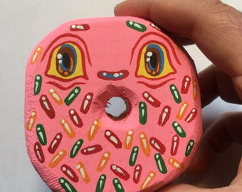 Pink and rainbow sprinkle missing tooth whittled doughnut