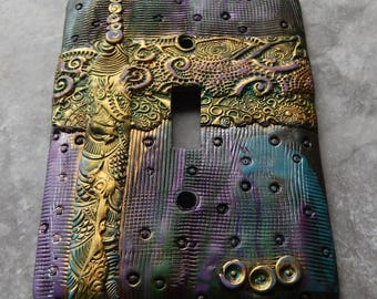 Golden Ribbons of Filigree, abstract polymer clay design on metal light switch cover, green, purple, blue, pink and gold accents