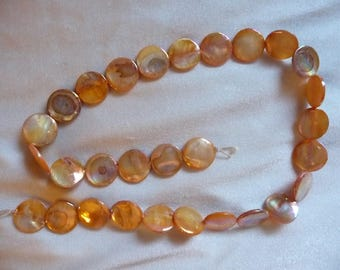 Bead, Mother of Pearl, 15mm Flat Round Coin, Shades of Orange, Very Shiny. Sold per 15 inch strand. There are 29 beads on the strand.