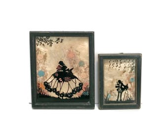 Pair of Miniature Silhouette pictures young man and woman in 18th century costume, dried flower background c1920