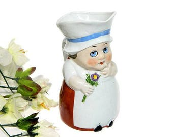 German Figural Pitcher Pudgy Googly Girl Holding Flower