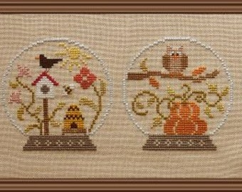 4 Seasons snow globe style – counted cross stitch chart to work in 16 colours of DMC thread. 4 seasonal motifs in snow globes. Four Seasons.