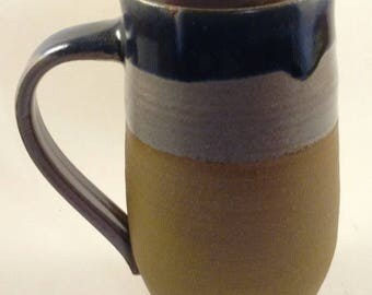 Pottery coffee mug in iron clay with red and blue layerd glaze