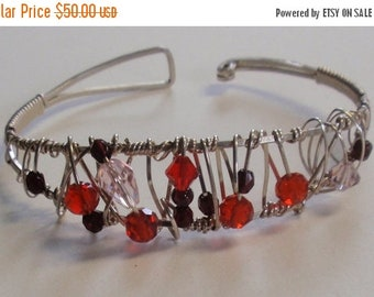 Crystal bangle bracelet with ruby red  beads are wrapped in sterling silver with garnet.  Back claps closure