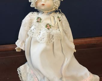 Porcelain doll in christening gown