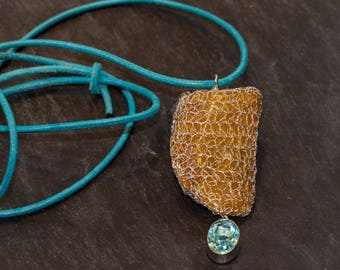 Necklace with crocheted amber with sterlingsilver set blue topas on leather band