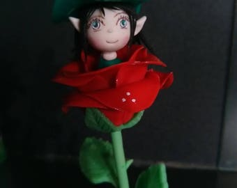 This Angel figurine: pixie one hidden in a red rose cold porcelain.