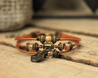 Bracelet ethnique multi-rangs avec cuir rond doré/cuivré, perles en verre aux reflets irisés, breloque bronze et mini perles ethniques
