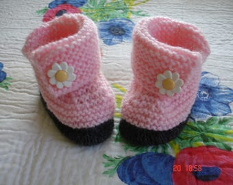 baby booties pink with dark gray sole edge.