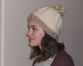 Winter white beanie hat with beige band and pompom from super soft acrylic yarn.