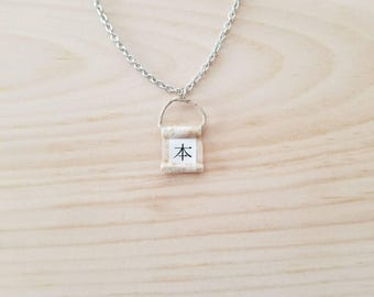Books in Japanese calligraphy on a minimal necklace
