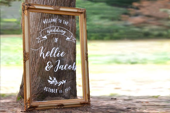 acrylic wedding sign framed in a gold gilded frame leaning against a tree