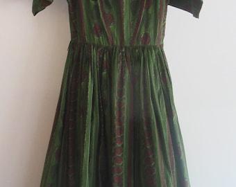 "Joan Miller Juniors, ""Let's Jitterbug"" in this pine green&chestnut panel printed cotton dress.  Dress below knee w/black netting underneath."