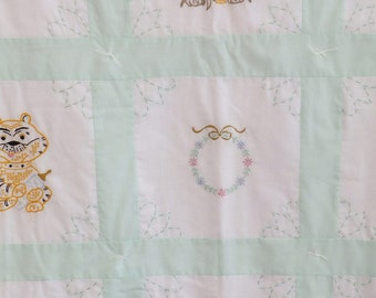 A hand embroidered green and white baby quilt