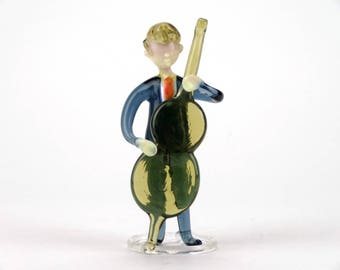 Mid century Bohemian glass cellist figurine sporting Donald Trump hairdo - Glass musician holding cello decorative item