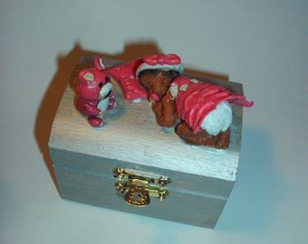 box is made of wood, silver, adorned with a baby girl