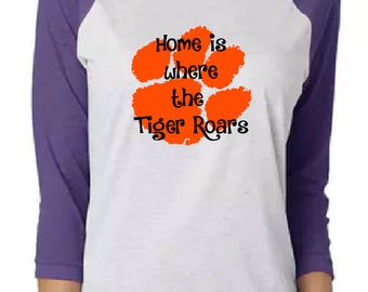 Home is where the tiger roars Raglan.  Tiger paw purple raglan shirt.  Great for sports fans.  Makes a great gift.
