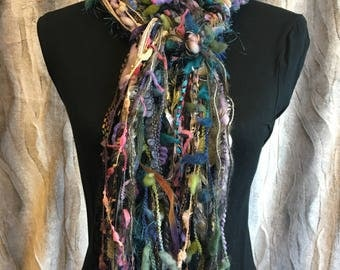 Unique fashion scarf in shades of green, purple, pink, cream, gold and black.
