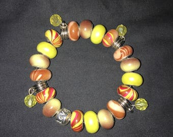 Yellow and brown bead bracelet with dangling charms