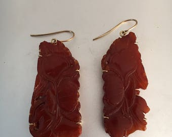 A pair of carved amber earrings Chinese Liao Dynasty 11th Century mounted in 14 carat gold.