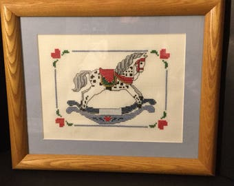 Crosstiched needlepoint picture of a rocking horse.With a light brown wood frame./nursery wall decor/ Childs room.