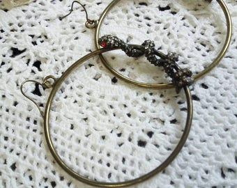 Brass hoops with red eyed slithering sparkling snakes