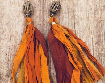 Orange hued silk tassel earrings with African brass bird cage beads