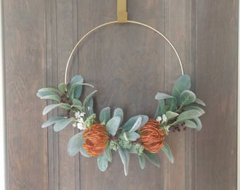 Modern gold greenery wreath with orange accents