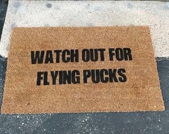 Watch out for flying pucks, balls, doormat,  hockey, baseballs, basketball, soccer, volleyball, sports