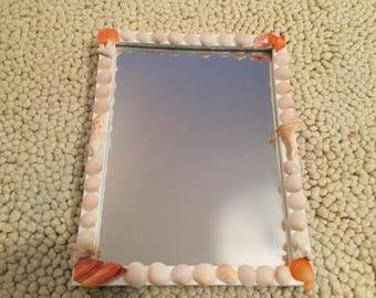 White and orange shell mirror.