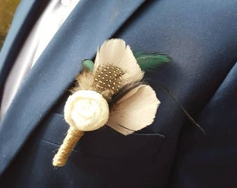 A beautiful bespoke feather boutonniere finished with a statement handmade velvet rose. Made by Glamour bouquets UK.