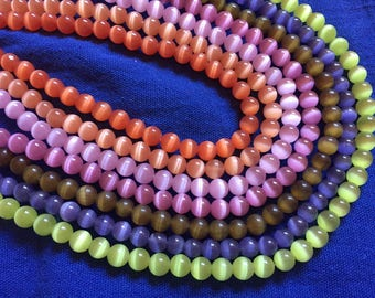 Assorted/mix 70 beads cat eye shimmering shades of pink, Orange, blue, green and coffee, cat's eye mix