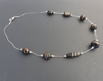 Black and gold necklace on snake chain