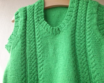 fine green sleeveless sweater knitted by hand for boy with cables on the front.